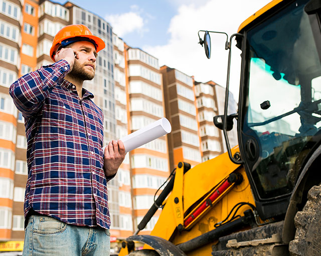 Bauarbeiter am telefonieren der neben einem Bagger steht.
